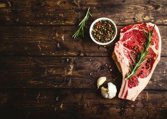 Kýta masa s rozmarýnem na dřevěném stole